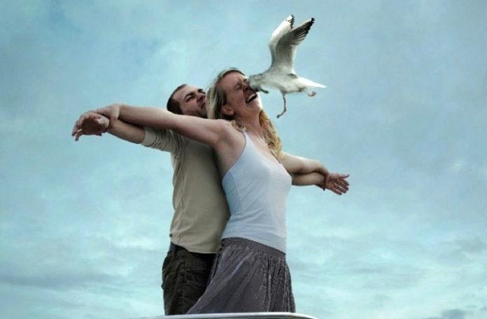 Kobieta i mężczyzna stojący na dziobie statku i ptak wlatujący w twarz kobiety