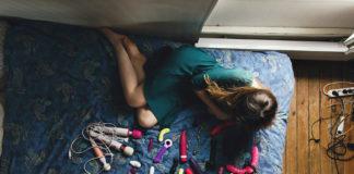 Ujęcie od góry na dziewczynę siedzącą na łóżku, naprzeciwko niej dużo wibratorów