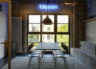Pomieszczenie z dużym stołem i neonem z napisem MISSION