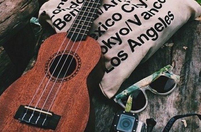 Gitara leżąca na ławce obok torba i okulary
