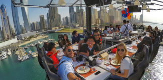 Zdjęcie przedstawiające grupę ludzi siedząca przy stole zawieszonym w powietrzu