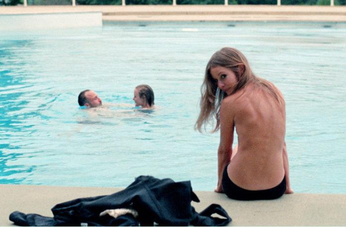 Dziewczyna topless w samych majtkach, siedząca nad brzegiem basenu