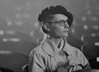 Czarno-białe zdjęcie kobiety siedzącej w kinie w płaszczu i berecie