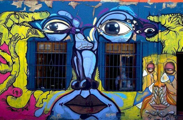 Kolorowy mural przedstawiający twarz - oczy, nos, usta, umieszczone między oknami budynku