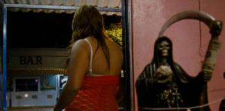 Kobieta stojąca tyłem do obiektywu i figurka postaci z kosą