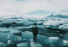 postać stojąca na unoszącej się na wodzie krze lodu