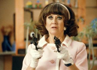 Kobieta ubrana w różową garsonkę trzyma w dłoniach dwa pistolety