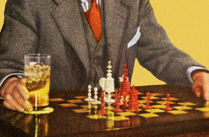 Mężczyzna w graniturze siedzący przy szachach, obok planszy stoi szklanka z napojem