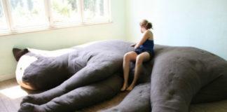 Wielka poduszka w kszatłcie kota i siedząca na niej dziewczyna