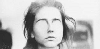 Czarno-białe zdjęcie dziewczyny, która ma wymazane oczy