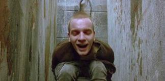Mężczyzna siedzący na toalecie w brudnym pomieszczeniu