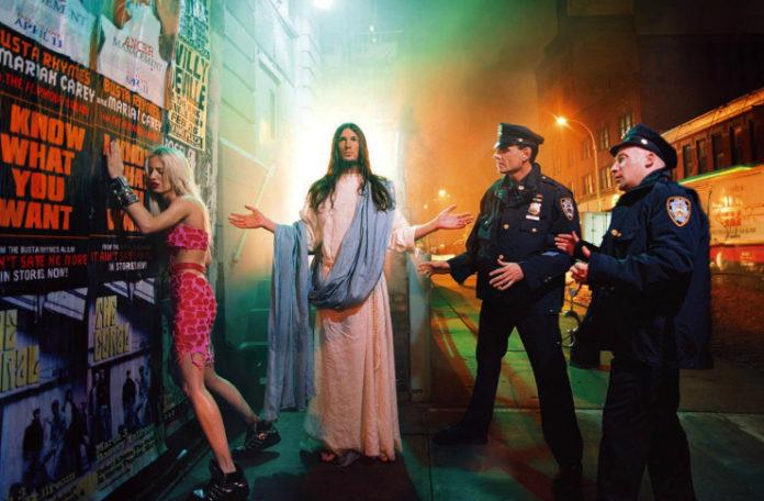 Mężczyzna przebrany za Chrystusa w towarzystwie dwóch policjantów i kobiety opartej o ścianę