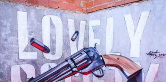 """Mural na ścianie przedstawiający napis """"LOVELY SOCIETY"""" i rewolwer"""