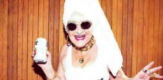 Uśmiechnięta starsza kobieta w okularach, ręczniku na głowie i białej koszulce
