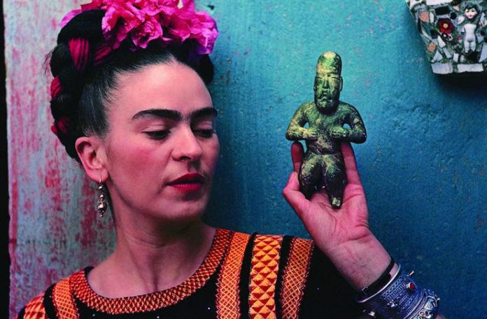 Kobieta z ciemnymi włosami z wplecionymi kwiatami, obok ręka trzymająca zieloną figurkę ludzika