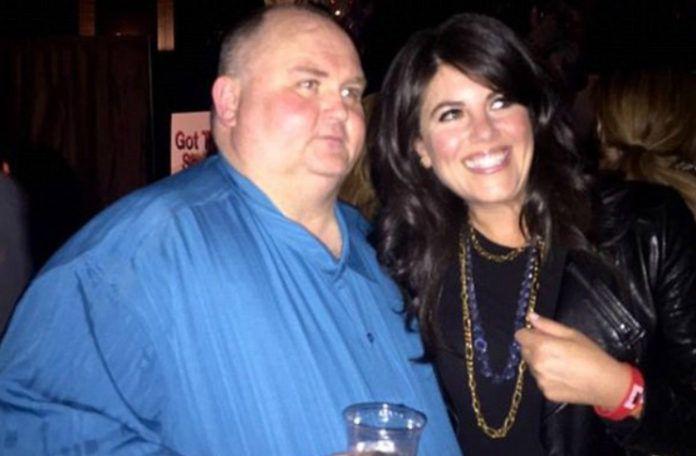 otyły mężczyzna w niebieskiej koszuli stojący obok brunetki w skórzanej kurtce