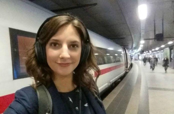 Brutnetka ze słuchawkami na głowie stojąca na tle pociągu