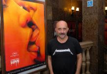 """Łysy mężczyzna w czarnej koszulce na tle plakatu do filmu """"Love"""""""