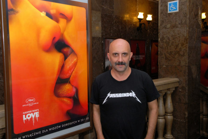 Łysy mężczyzna w czarnej koszulce na tle plakatu do filmu