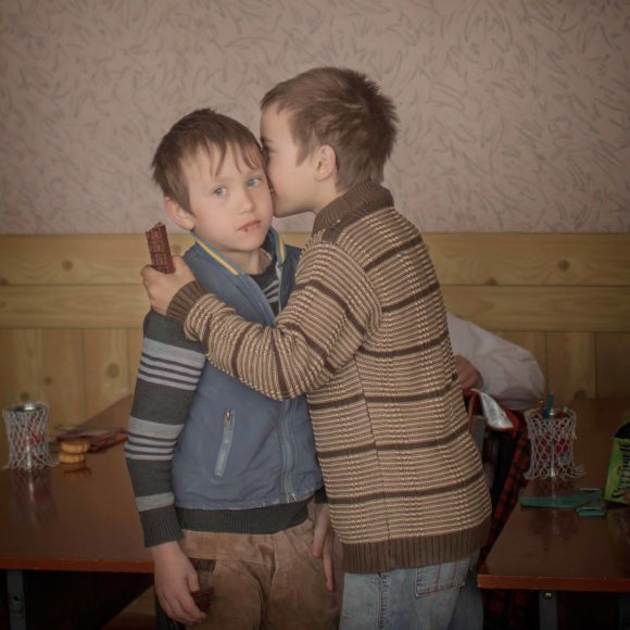"""140324 Igor and his friend Renat has an intimate moment of friendship in the classroom. Igor celebrates his ninth birthday and their grandmother bought chocolate for the the boys and their friends. """"I wish a pair of boxinggloves for my birthday, says Igor."""" Igor also have a twinbrother and when they were only two years old their mother travelled to Moscow to work in the construction field. Three weeks later they found out that she died in a hemorrhage and they have no father. Thousands of children grow up without their parents in the Moldovan countryside. Some villages have turned into ghost towns. Young people have fled the country, leaving an dwindling, elderly population and young children. Schools are forced to close and whole villages are erased on the map. Some of them will never meet their parents again. For the children of Moldova, the future is uncertain."""