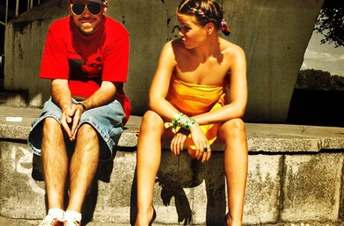 Chłopak i dziewczyna siedzący na poręczy