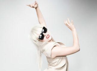 Jasna blondynka z podniesionymi rękami w jasnej bluzce i dużych, ciemnych okularach