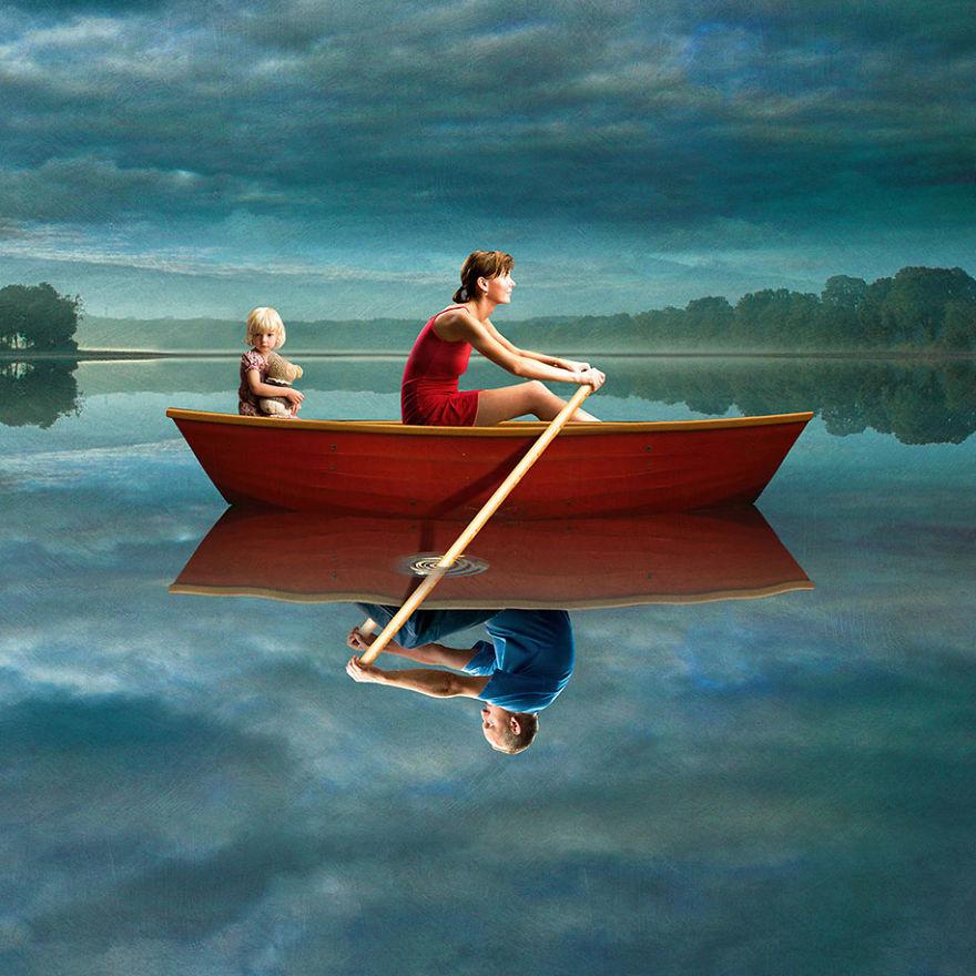 surrealistyczna grafika Igora Morskiego, matka w czerwonej sukience siedzi w czerwonej łódce z córeczką przytulającą misia, w odbiciu wody w łódce siedzi ojciec w niebieskiej koszulce, oboje chcą wiosłować