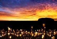 Zachód słońca, w tle skała, na pierwszym planie lampki ledowe