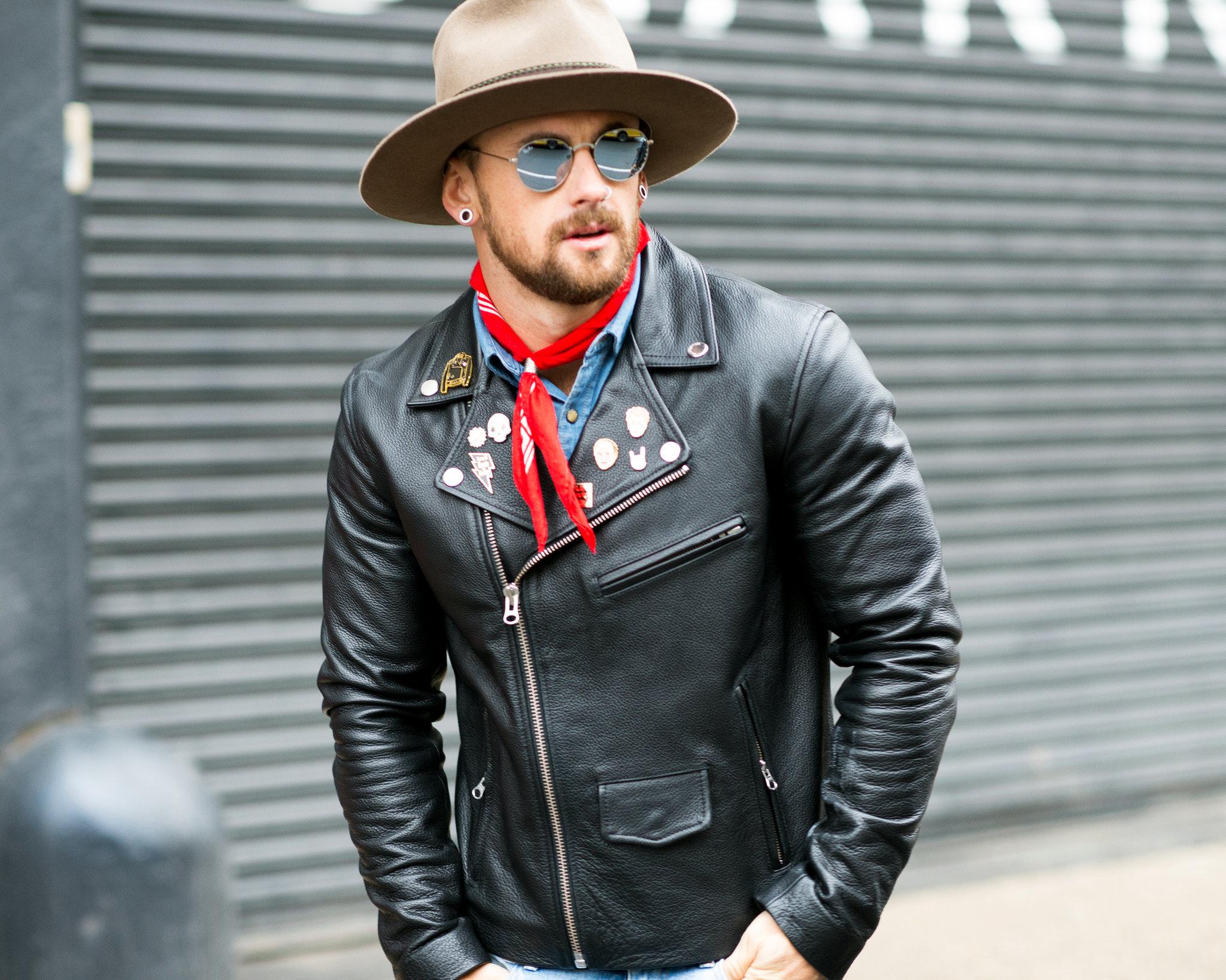 Młody mężczyzna w skórzanej kurtce, kapeluszu i okularach