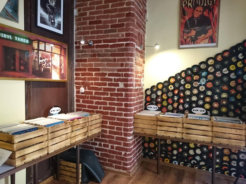 wnętrze antykwariatu vinyl tamka, skrzynki z płytami, płyty na ścianie, plakat the prodigy