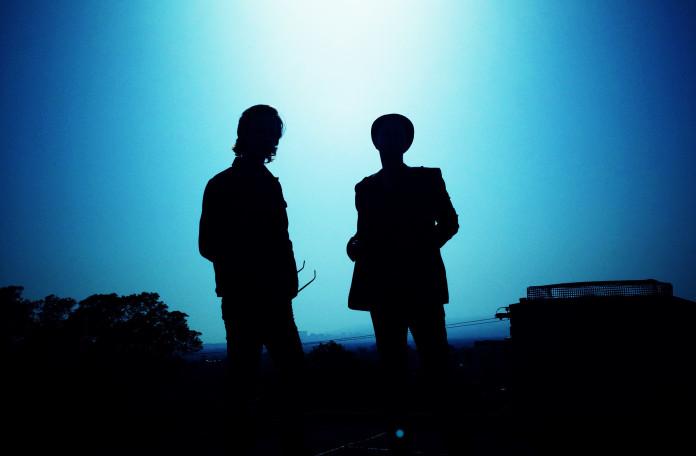 cienie dwóch dj-ów na niebieskim tle