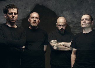 łysi muzycy w czarnych koszulkach na ciemnym tle