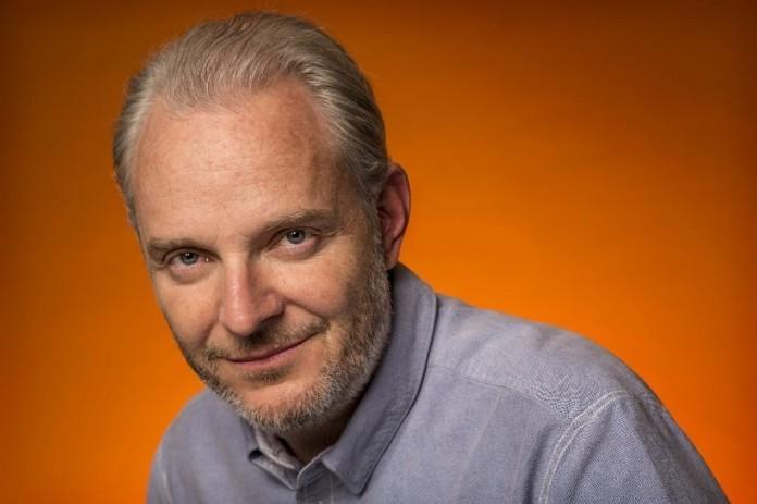 reżyser francis lawrence w niebieskiej koszuli na pomarańczowym tle