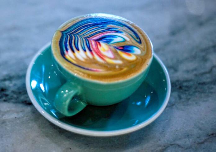 niebieska filiżanka, wypełniona kawą z kolorowym wzorem na wierzchu
