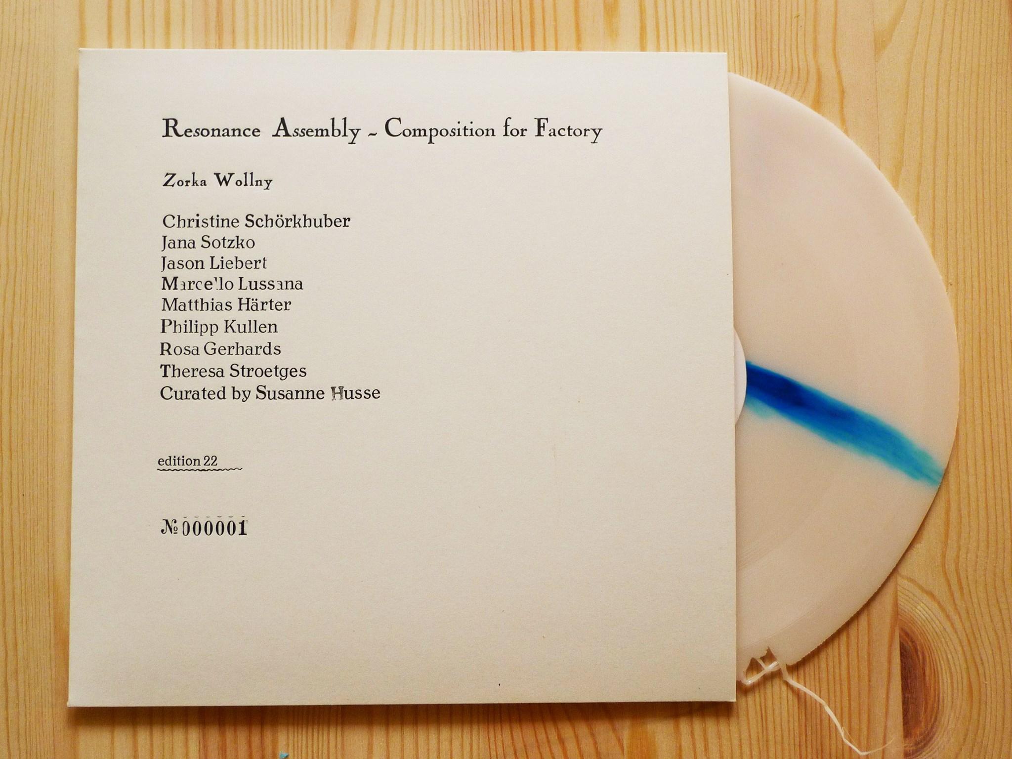 płyta resonance assembly - composition for factory leżąca na drewnianym biurku w okładce