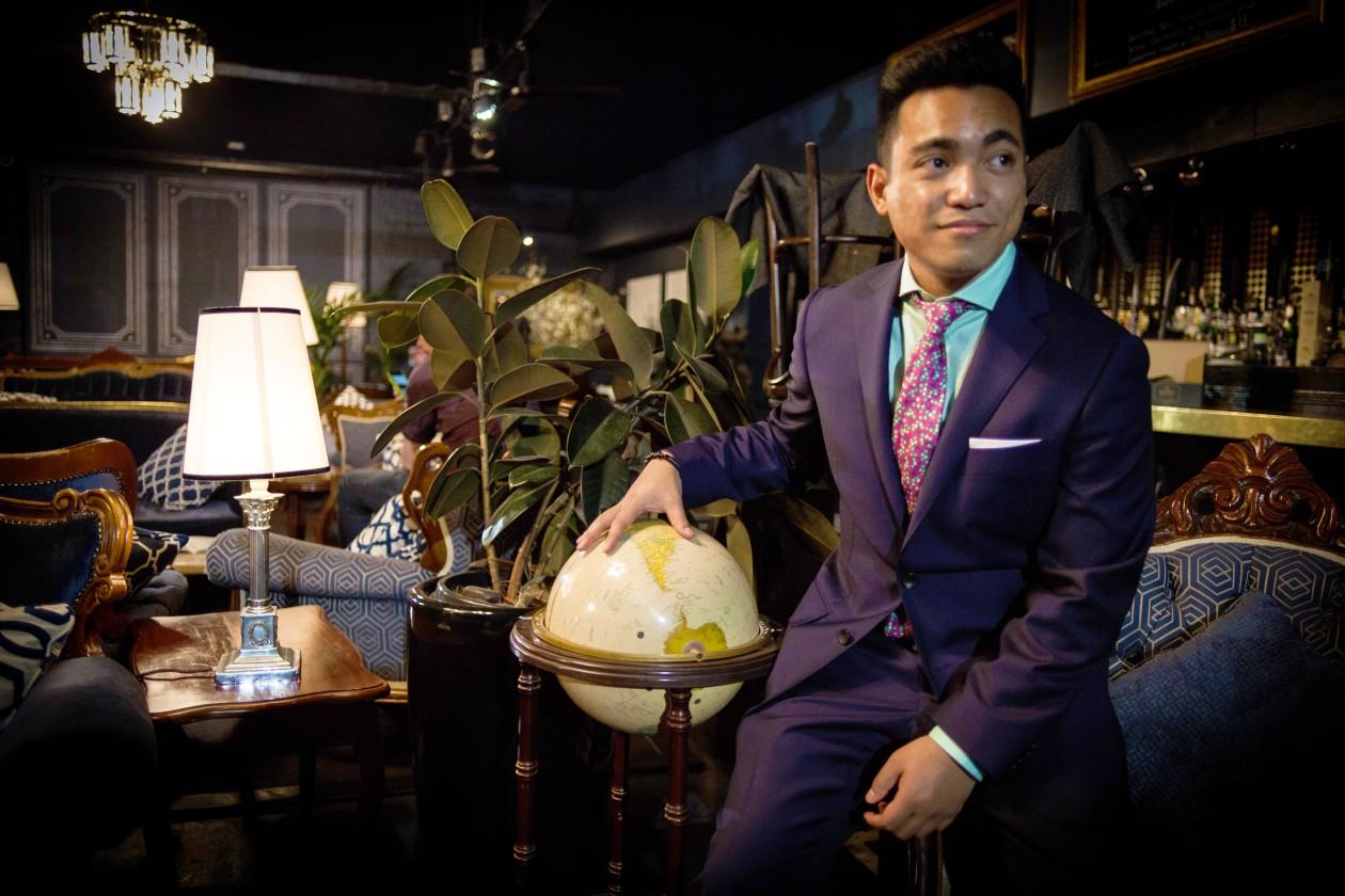 mężczyzna ubrany w fioletowy garnitur w ciemnym eleganckim pomieszczeniu