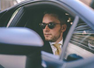Młody mężczyzna, elegancko ubrany w czarnym samochodzie, wygląda przez otwarte okno