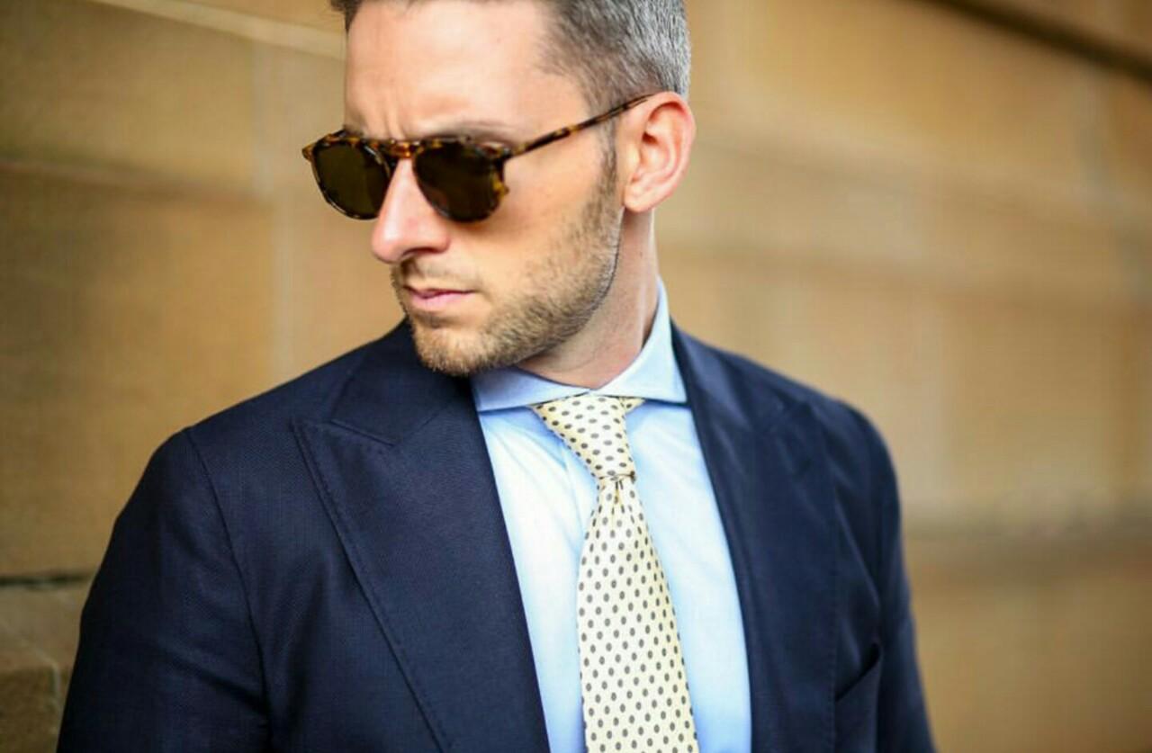 Młody elegancki mężczyzna, w jasnoniebieskiej koszuli, granatowej marynarce z krawatem i w okularach przeciwsłonecznych