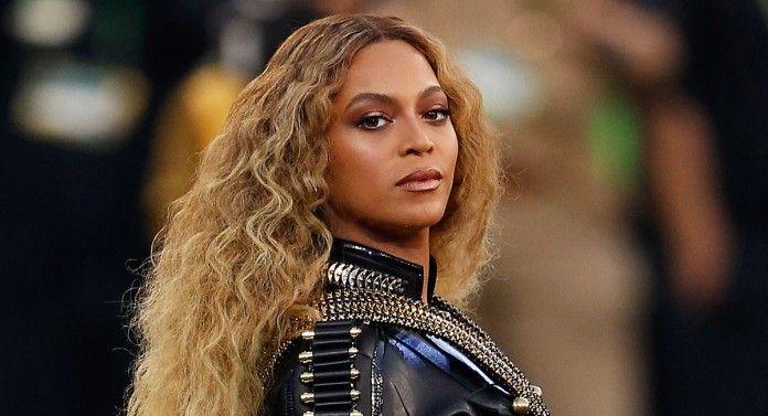 Beyonce z długimi kręconymi włosami, ubrana w skórę a la militarną