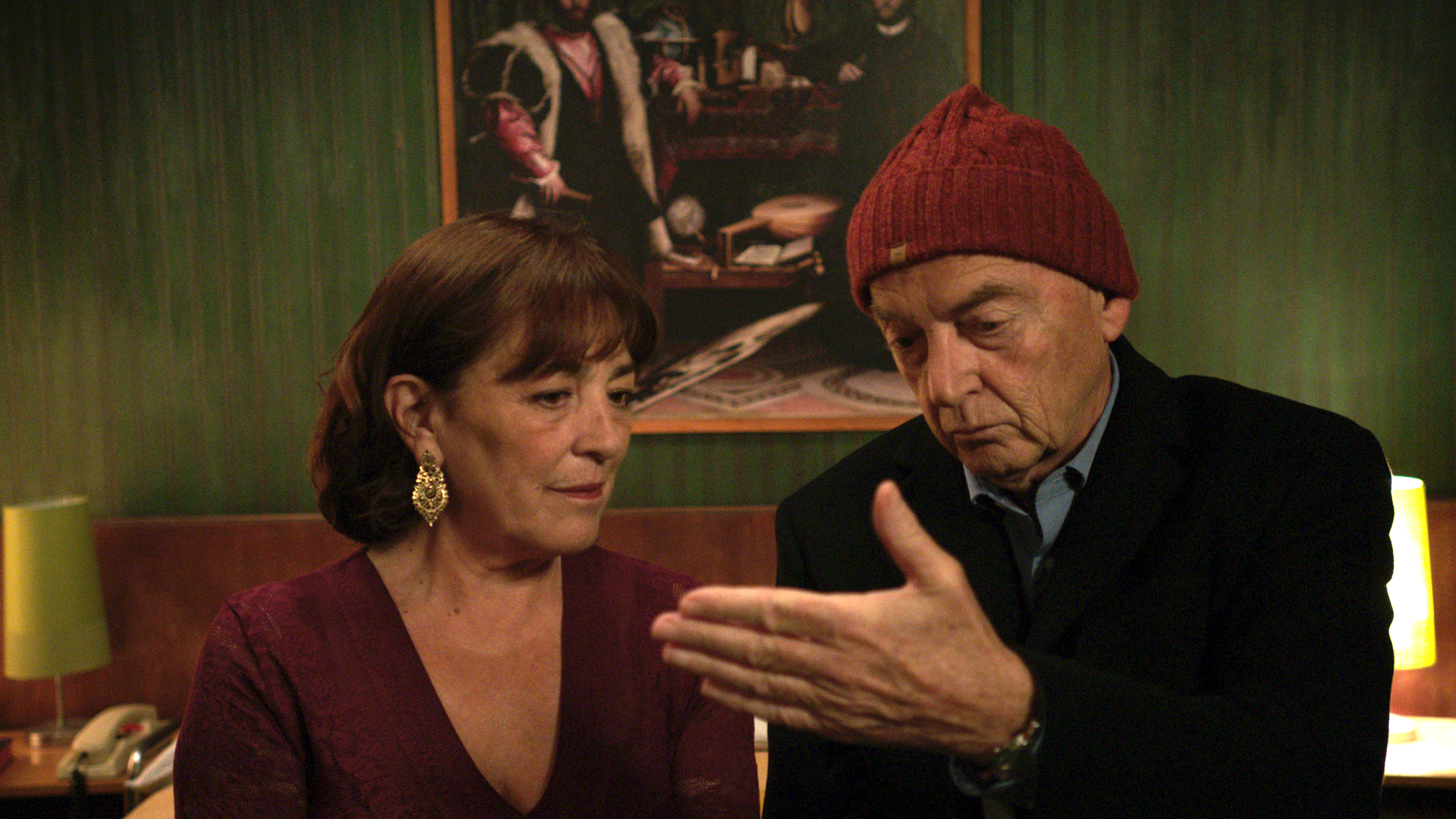 Kadr z filmu Pycha, starszy mężczyzna oraz kobieta siedzą, patrząc na rękę mężczyzny