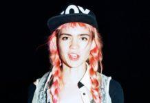 Grimes w czapce z daszkiem z napisem boy, różowych włosach w warkoczykach, czarne tło