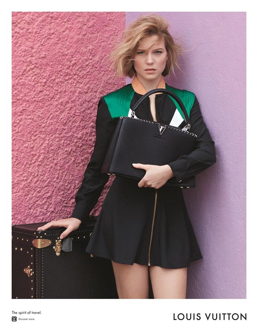 Młoda dziewczyna, z krókimi blond włosami stoi trzyma torbę i stoi obok walizki na tle różowej i fioletowej ściany