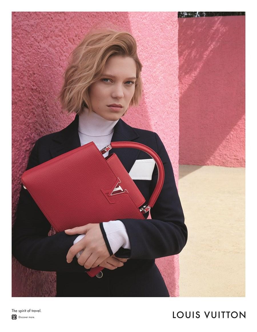 Młoda dziewczyna, ubrana w golf, trzyma czerwoną torbę marki Louis Vuitton