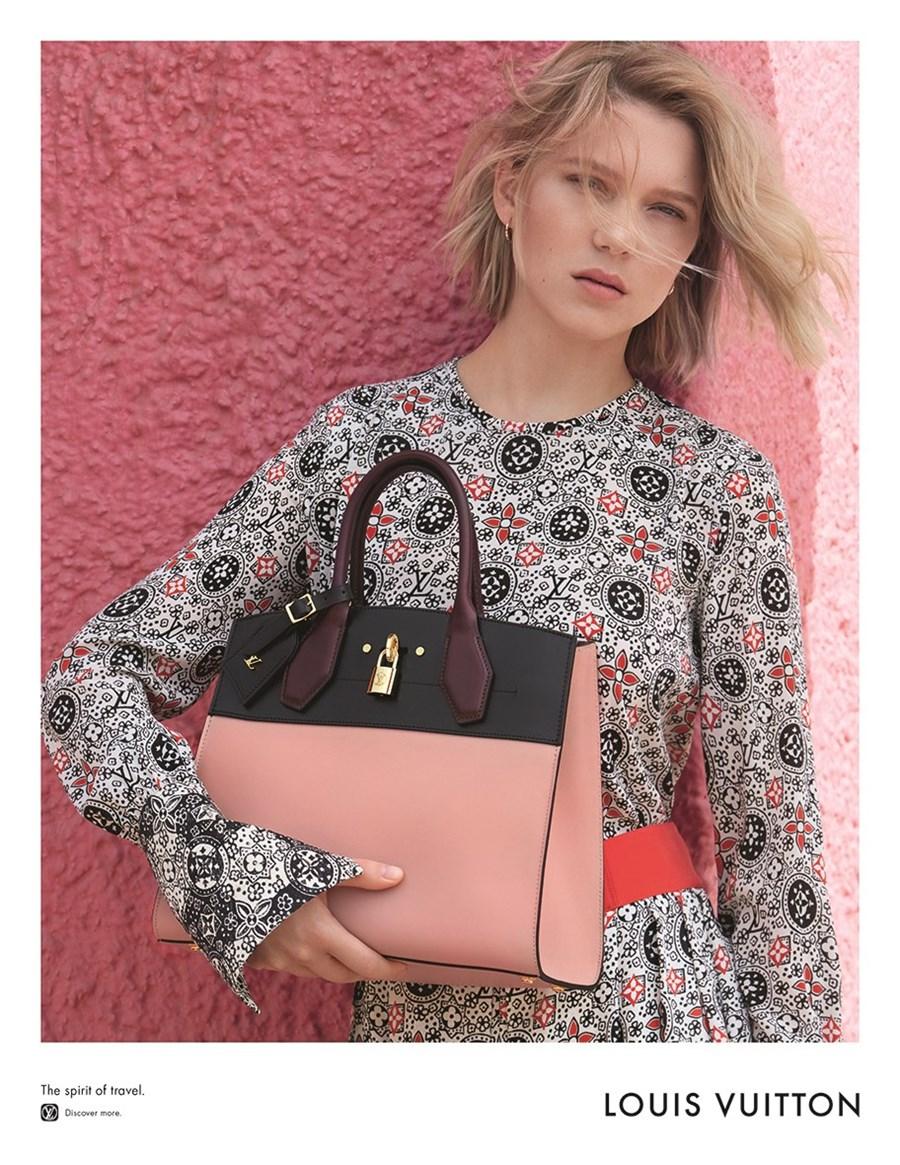 Młoda dziewczyna, trzyma różową torbę, ubrana w delikatną sukienkę , stoi na tle różowej ściany