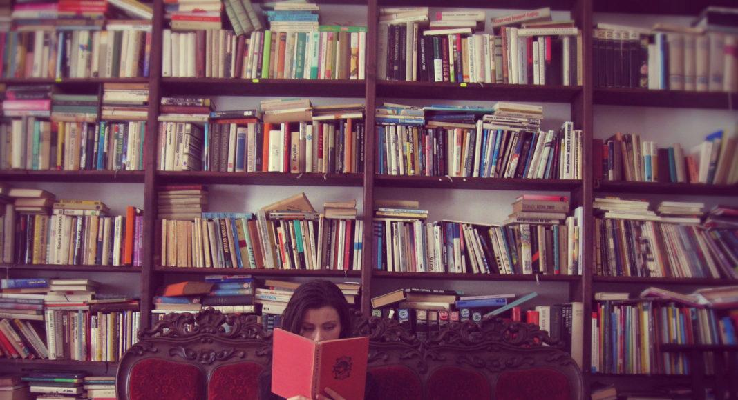 dziewczyna z ksiazka w bibliotece na kanapie