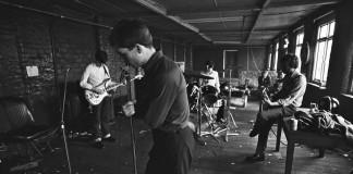 joy division grający w salce prób, ian curtis z mikrofonem stoi z przodu, zdjęcie czarno-białe