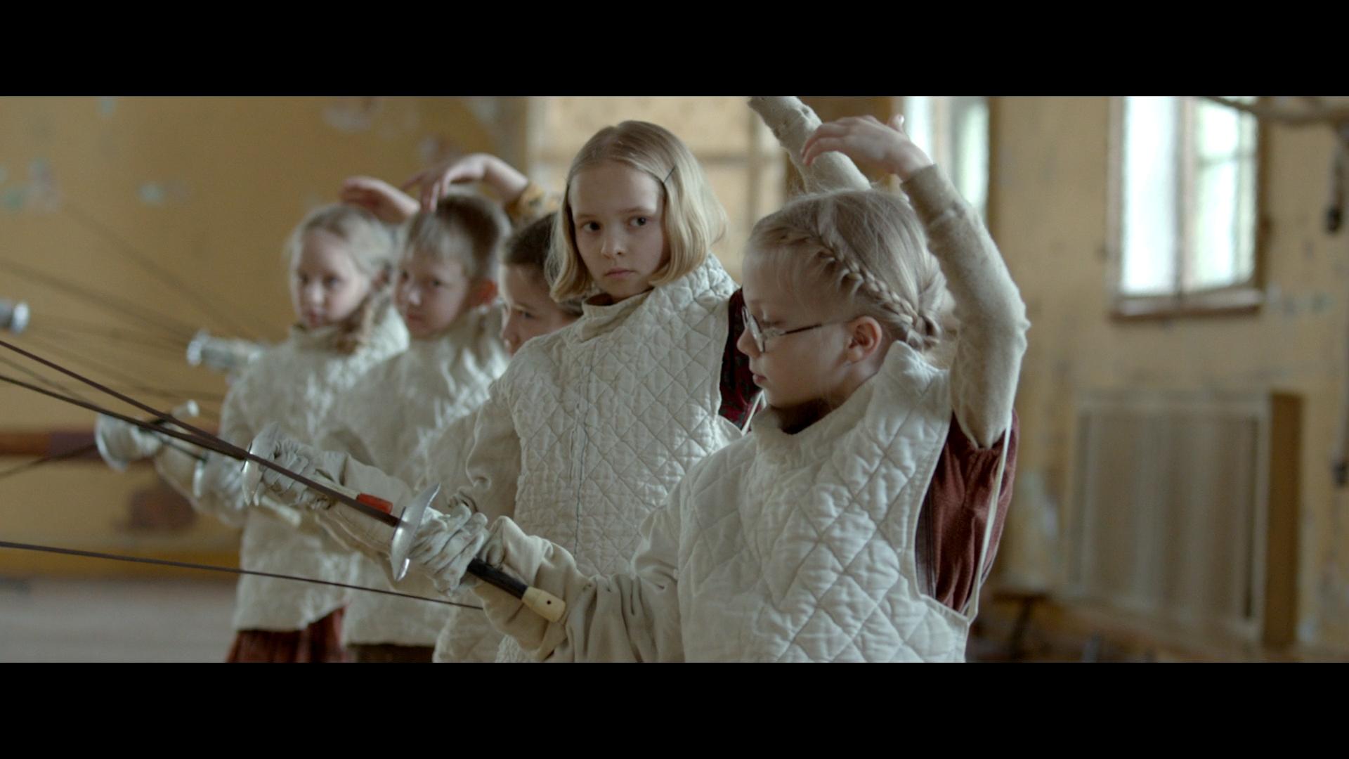 film Szermierz, dzieci ćwiczące szermierkę, dwie młode dziewczynki