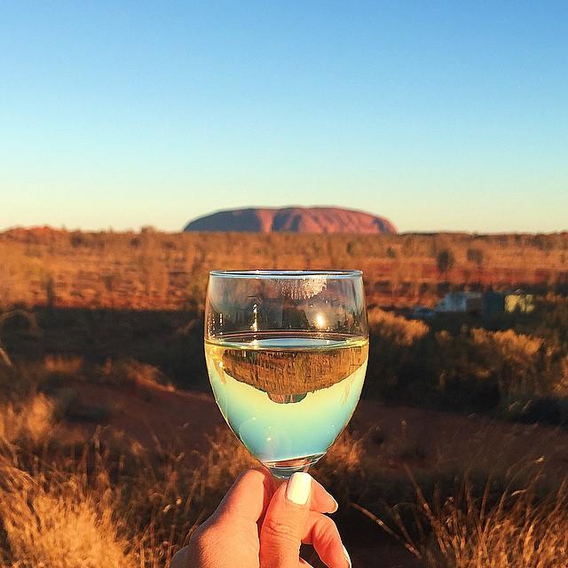 Kieliszek białego wina na tle Uluru w Australii