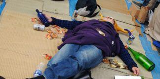 Kobieta leżąca na podłodze pełnej śmieci, butelek