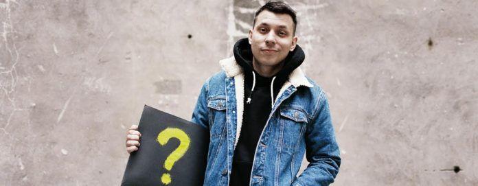 raper Bisz na tle ściany w ręce ma opakowanie ze znakiem zapytania
